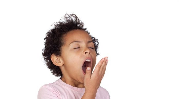 Image of a child yawning on a white background