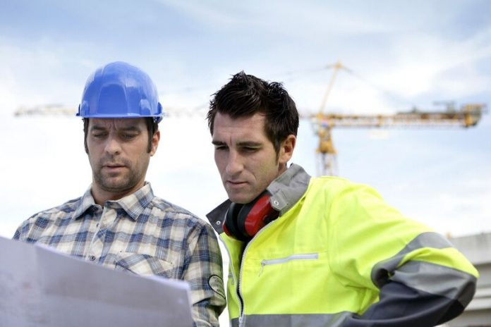 Image of two people checking drawings of a build